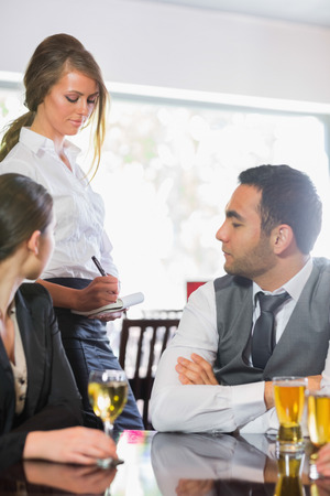 Business people ordering a dinner from waitress in the restaurant photo