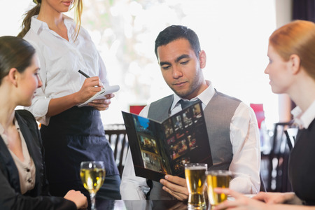 Handsome businessman ordering dinner from waitress in a restaurant photo