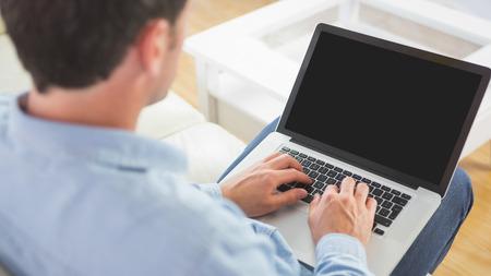 Blick �ber die Schulter von Casual Mann mit Laptop in helles Wohnzimmer Lizenzfreie Bilder