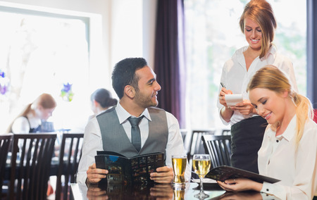 Business people reading menu and ordering in a restaurant photo
