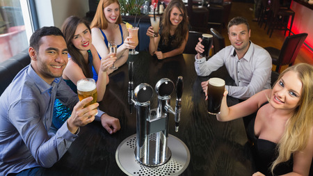 beer pump: Young friends sitting together and raising their pints looking at camera