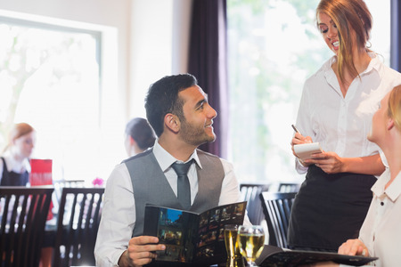 alcohol server: Handsome businessman ordering food from waitress in a restaurant