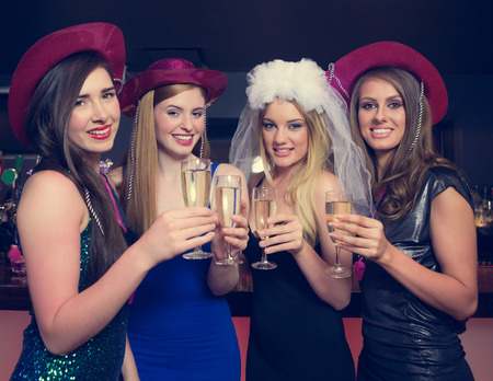 hen party: Attractive friends clinking champagne glasses at hen night looking at camera