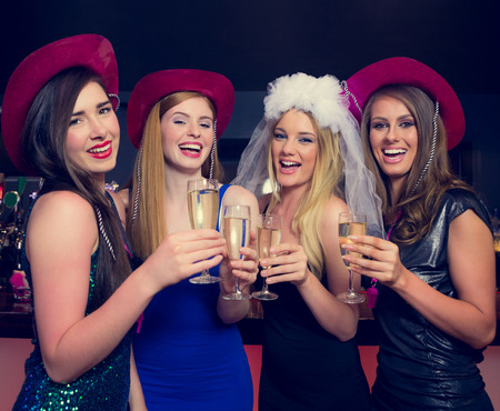hen party: Laughing friends clinking champagne glasses at a hen night looking at camera