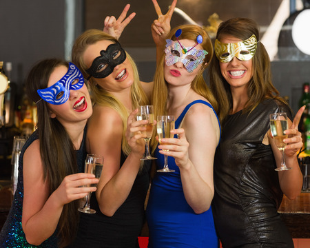 hedonism: Attractive women wearing masks holding champagne looking at camera Stock Photo