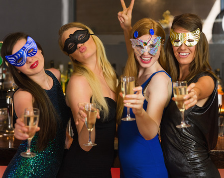 hedonistic: Happy friends wearing masks showing champagne glasses and posing