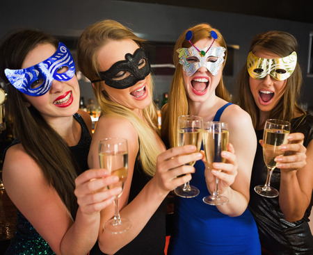 hedonism: Attractive friends with masks on holding champagne glasses laughing at camera Stock Photo