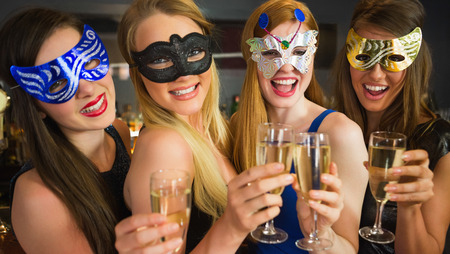hedonistic: Smiling friends holding champagne glasses wearing masks looking at camera