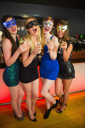 hedonism: Laughing friends with masks on holding champagne looking at camera Stock Photo
