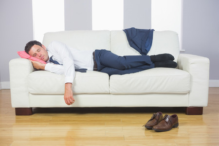 Calm handsome businessman sleeping on couch after work at home photo