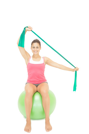 gleeful: Gleeful sporty brunette stretching with resistance band on white background Stock Photo