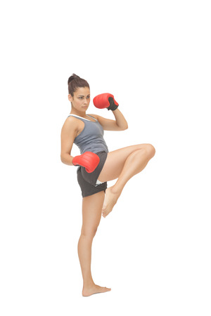 Concentrating sporty brunette kick boxing on white background photo
