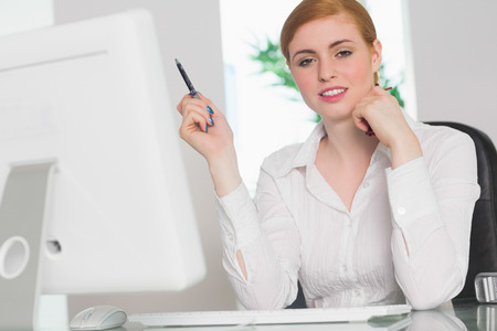 Stern businesswoman working at her desk holding pen in her office Stock Photo - 26743493