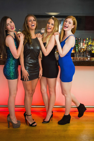 Laughing friends posing and looking at camera in a nightclub photo