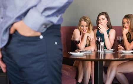 Three pretty friends checking out mans rear in a nightclub photo