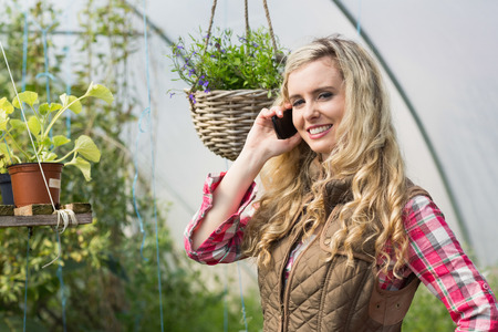 smiling woman in a greenhouse: Happy woman mobile phoning in a green house and looking at the camera Stock Photo
