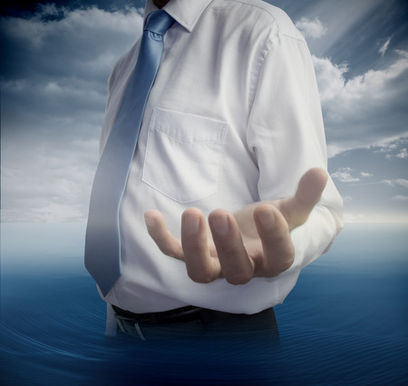 open palm: Mid section of man showing open hand on sky background
