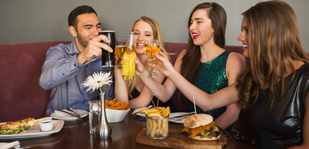 clinking: Amigos que cenan juntos y tintineo de vasos en el restaurante Foto de archivo