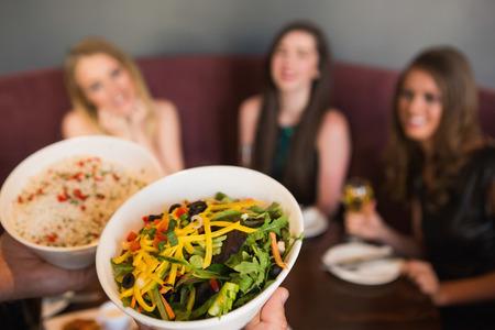 bringing: Waiter bringing the salad to hungry customers