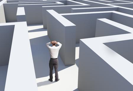 キャプチャされている迷路の中で立っている実業家の背面図