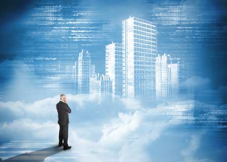 cloud industry: Rear view of businessman standing under holographic city on blue background Stock Photo