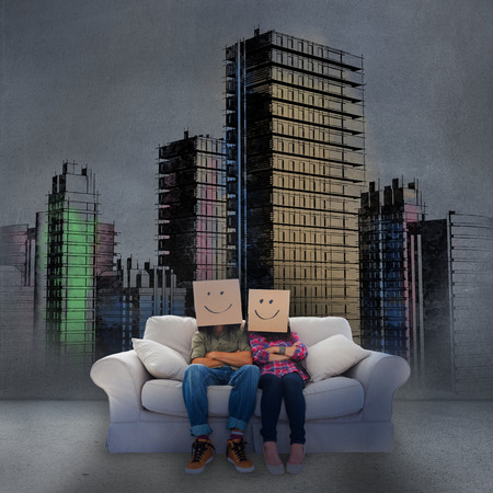 dimly: Couple sitting on couch in front of painted city in dimly light Stock Photo