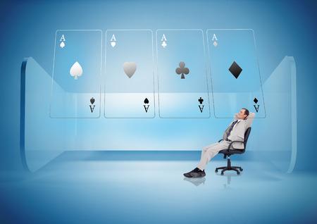 jeu de carte: Homme d'affaires sur chaise pivotante regardant cartes holographiques en lumière bleue Banque d'images