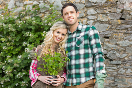 Couple standing in a garden holding a plant smiling at camera photo