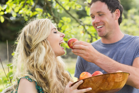 Young man feeding his girlfriend with an apple while laughing photo