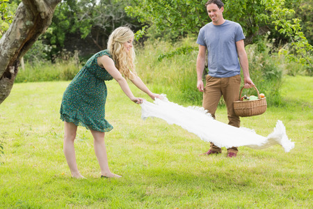 Blonde woman spreading a blanket for a picnic with her boyfriend outside on sunny day photo