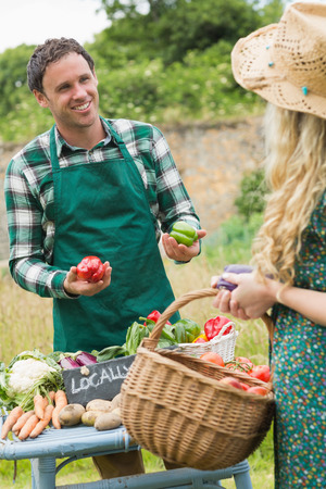 Young handsome farmer selling organic vegetables to pretty blonde at a farmers market photo