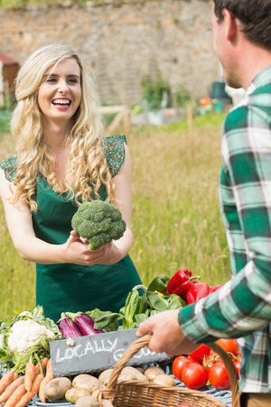 Young female farmer selling organic broccoli to a young man  photo