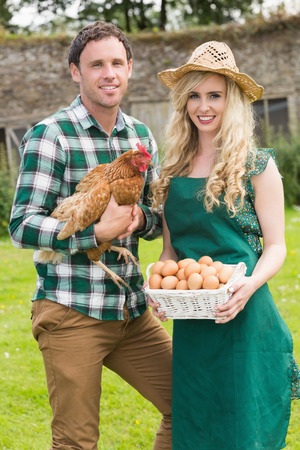 Happy young couple holding chicken and basket of eggs in their garden photo
