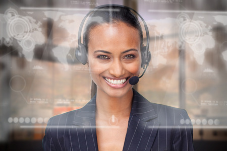 Portrait of a beautiful ethnic businesswoman with a headset on smiling at the camera photo