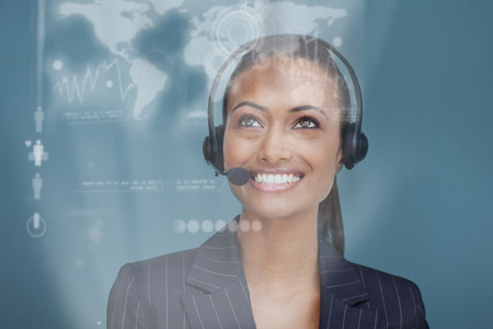 Portrait of a beautiful ethnic businesswoman with a headset on looking upwards photo