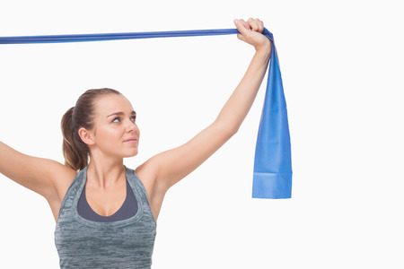 blue toned: Ponytailed young woman training using a resistance band n white background