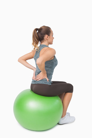 hair tied back: Blonde ponytailed woman touching her back sitting on fitness ball
