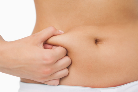 mujeres gordas: Mujer delgada joven con poca grasa en su vientre sobre fondo blanco Foto de archivo