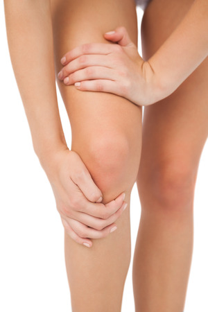 injured knee: Close up of slim woman touching her injured knee on white background