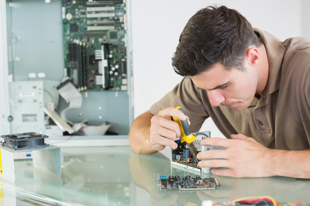 computer hardware: Handsome serious computer engineer repairing hardware with pliers in bright office Stock Photo