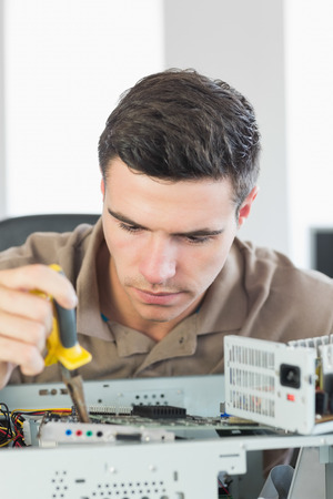 it technician: Handsome focused computer engineer repairing open computer in bright office Stock Photo
