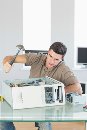 wrath: Handsome angry computer engineer destroying computer with hammer in bright office Stock Photo