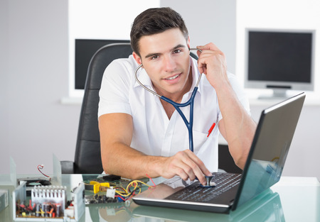 Handsome smiling computer engineer examining laptop with stethoscope in bright office photo