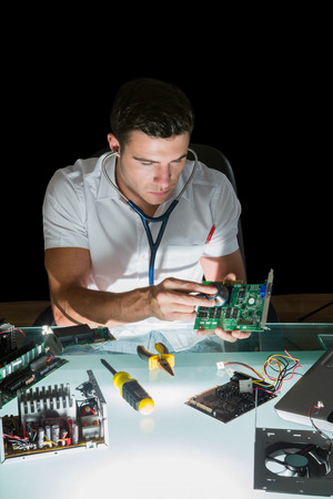 Attractive computer engineer examining hardware with stethoscope by night at his lit desk photo
