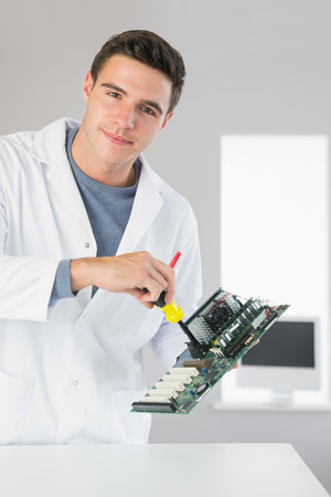 Attractive content computer engineer repairing hardware with screw driver in bright office