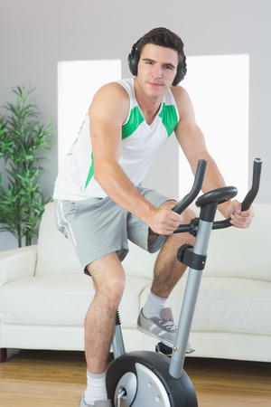 Content handsome man training on exercise bike listening to music in bright living room photo