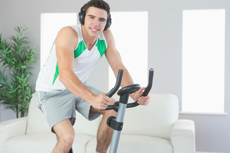 Smiling handsome man training on exercise bike listening to music in bright living room photo