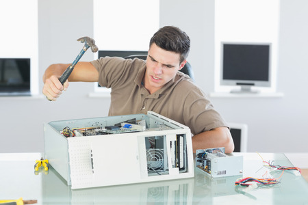 destroying: Attractive angry computer engineer destroying computer with hammer in bright office