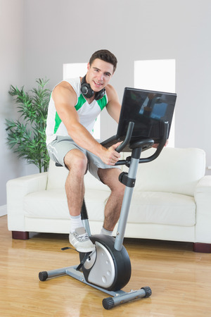 Smiling handsome man training on exercise bike using laptop in bright living room photo