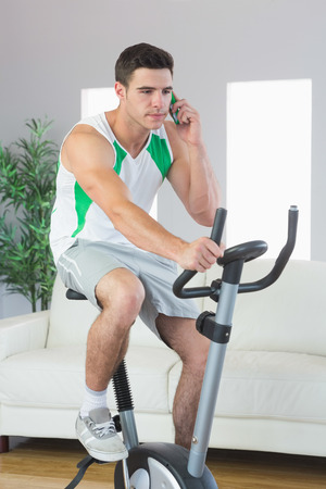 Stern handsome man training on exercise bike phoning in bright living room photo